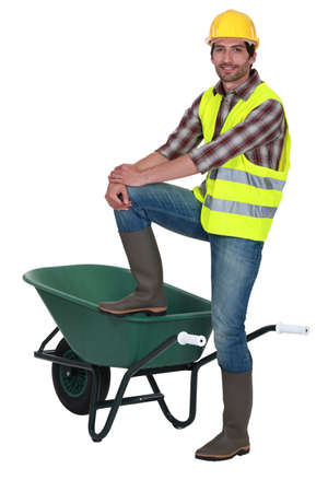 Man stood with one foot on wheelbarrow photo