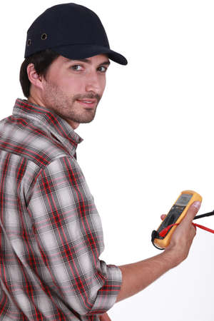 multimeter: Tradesman holding a multimeter Stock Photo