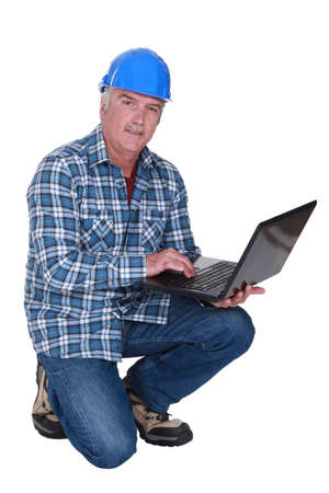 knees bent: Artisan greater with laptop Stock Photo