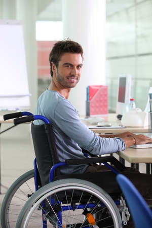 Man in wheelchair working at computer photo