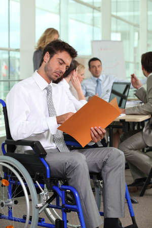 A group of business people in a meeting room, one of them in a wheelchair  photo