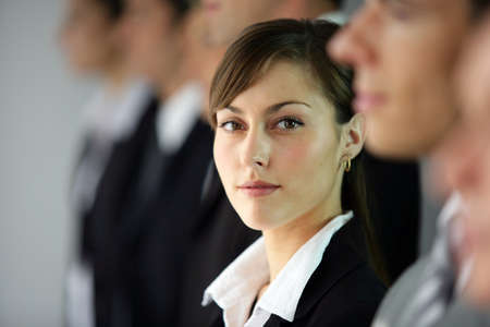 managing: Young woman standing in line with co-workers