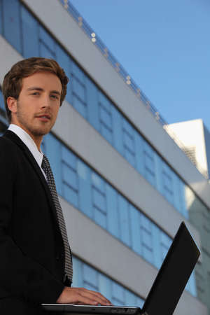 Young businessman outside a modern office building photo