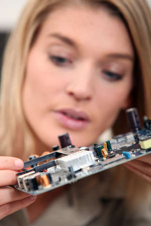 Woman fixing a motherboard photo