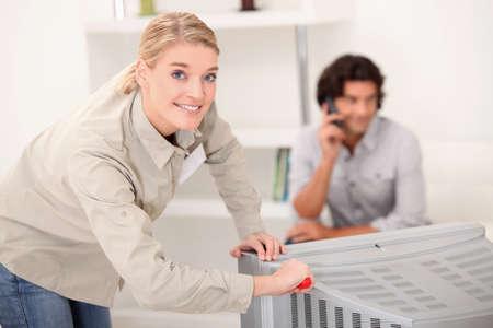 Woman fixing a television set photo