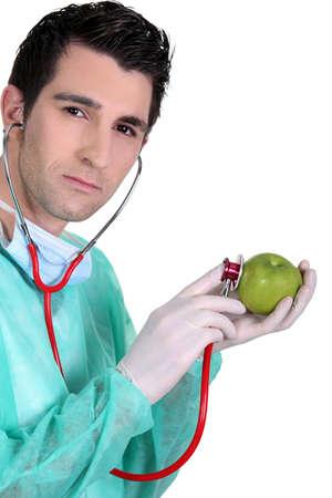 Male nurse listening to apple heartbeat photo