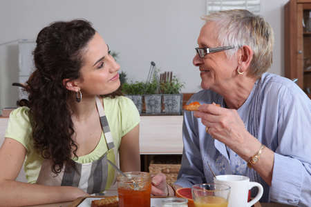 domiciles: elderly dame and young brunette having breakfast Stock Photo