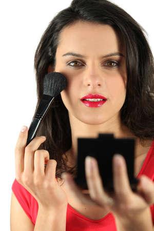 blusher: Brunette applying blusher Stock Photo