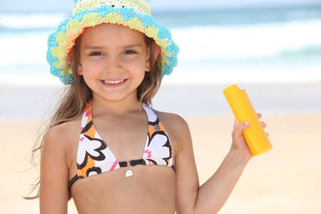 Young girl on the beach holding suncream photo