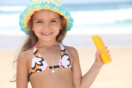suntan lotion: Young girl on the beach holding suncream
