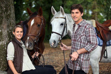 young couple and horses in forest photo