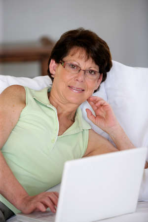 50 55 years: Woman using her laptop in her living room