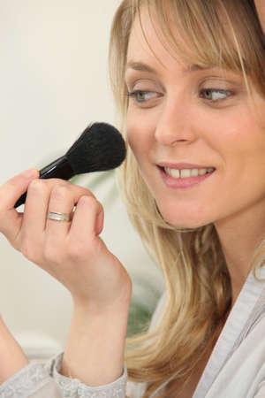 blusher: Young woman applying blusher Stock Photo
