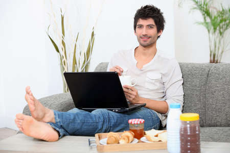 stretched out: young man seated on a sofa with legs stretched out, doing computer and eating breakfast,