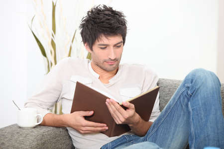 Man reading a book on a sofa Stock Photo - 12529671