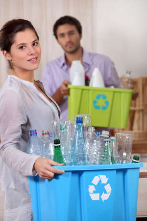Young woman and boyfriend recycling plastic photo