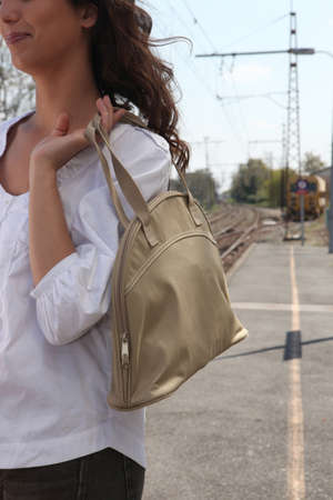 Woman with a large handbag waiting for a train photo