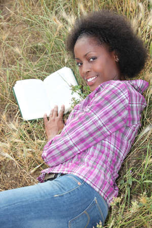 Woman laid in field reading book photo