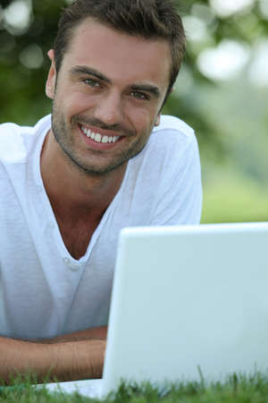 Smiling man outdoors with a laptop photo