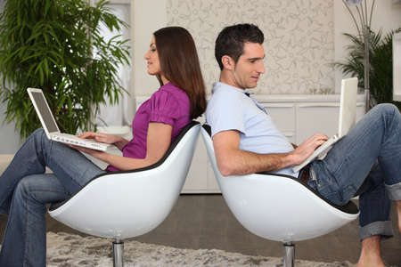 Man and woman sitting back to back using computers Stock Photo - 12529448