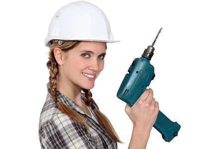 tradeswoman: Smiling tradeswoman holding a power tool