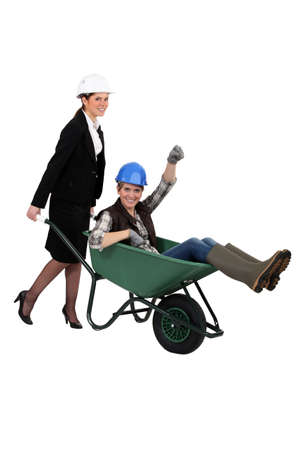 Woman pushing fellow worker in wheelbarrow photo