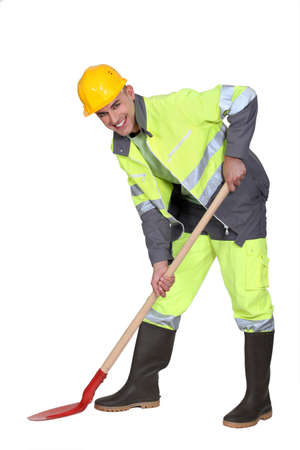bricklayer all smiles with shovel against studio background photo