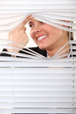 snoop: Nosy woman peering through some blinds Stock Photo