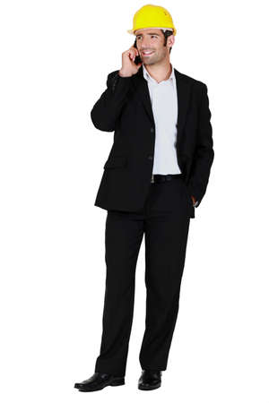 businessman wearing helmet and talking on his cell Stock Photo - 12528946