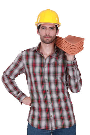 Builder holding stack of roof tiles photo