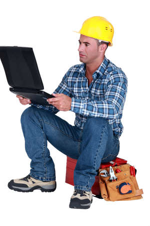 Distraught tradesman reading his emails photo