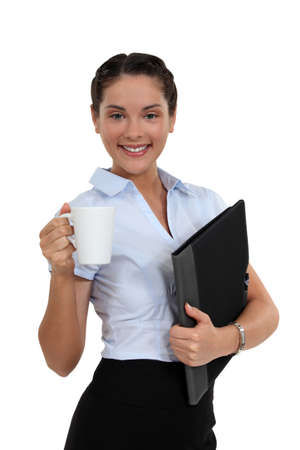 yucca: Brunette worker with cup of coffee and folder