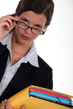 watch over: Observant woman peering over her glasses Stock Photo