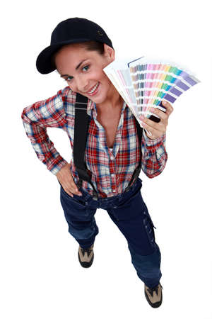 displaying: Woman displaying paint colour samples