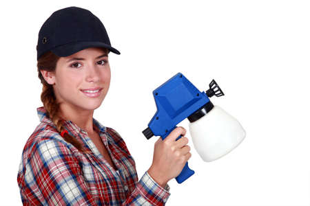 Woman holding spray for painting photo
