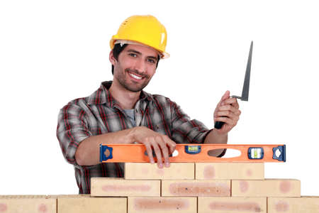 A mason checking a wall with a level  photo