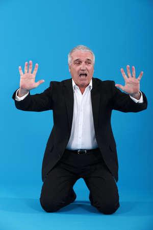 Kneeling senior man in suit screaming Stock Photo - 12529865