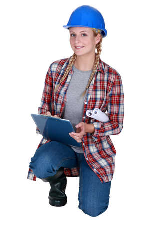 Female construction worker kneeling with clip-board Stock Photo - 12529902