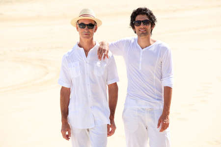 causal clothing: Father and son stood on beach
