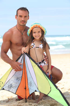 Little girl and father at the beach photo