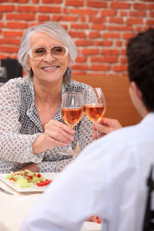 Young man and senior woman having lunch in a restaurant photo