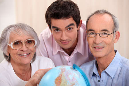 grown: Grown-up family looking at a globe