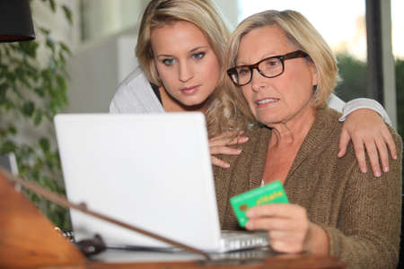 carte: Older woman using a card online Stock Photo