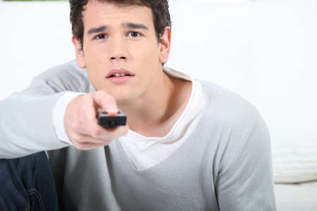 spare time: young man using a remote controller Stock Photo