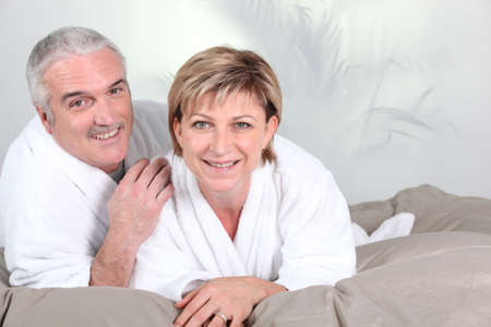 Couple lying in bed after a shower photo