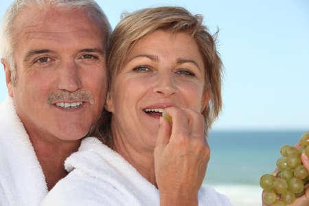 mature woman in bathrobe at spa resort eating grapes with husband photo