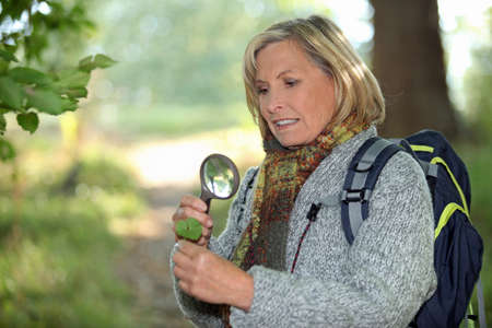 55 to 60: Woman looking through magnifying glass