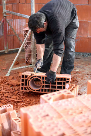 Workman sculpting a brick photo