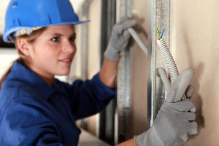 workwoman: Tradeswoman installing electrical wiring