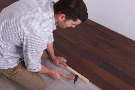 Man laying a hardwood floor photo